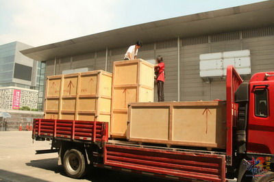 区��cj��'�)�9b$_一辆载有多个大型木箱的卡车驶入上海cj展区后院